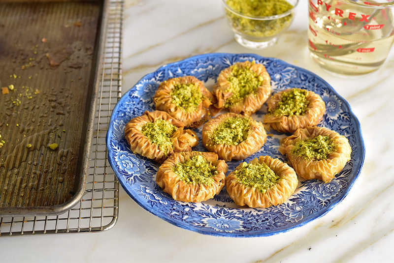 Pistachio baklawa nests on a blue serving plate
