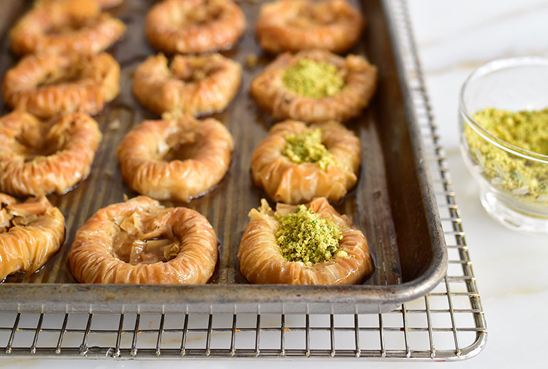 Pistachio baklava nests filled with pistachio on a sheet pan