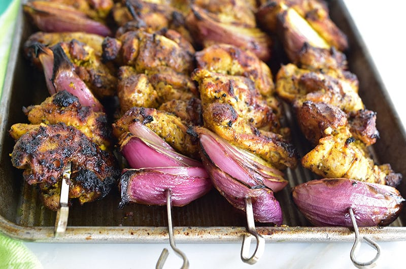 Grilled Chicken Shawarma Skewers with red onion on a sheet pan