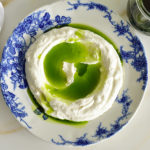 Basil oil poured over labneh in a blue dish