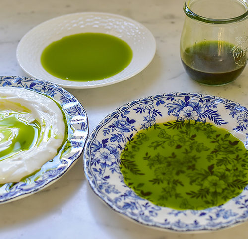 Basil oil in three plates on the counter