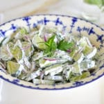 Cucumber salad with herbs in a blue and white bowl