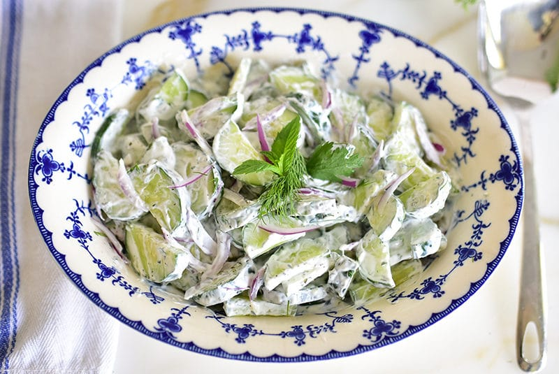 Cucumber salad with herbs in a blue bowl with a spoon