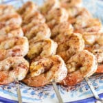 Garlicky Sumac Shrimp skewers on a blue plate