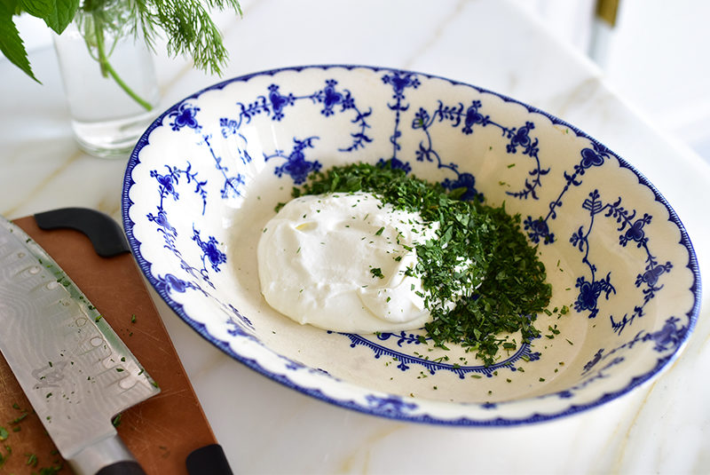 A blue and white bowl filled with labneh and herbs