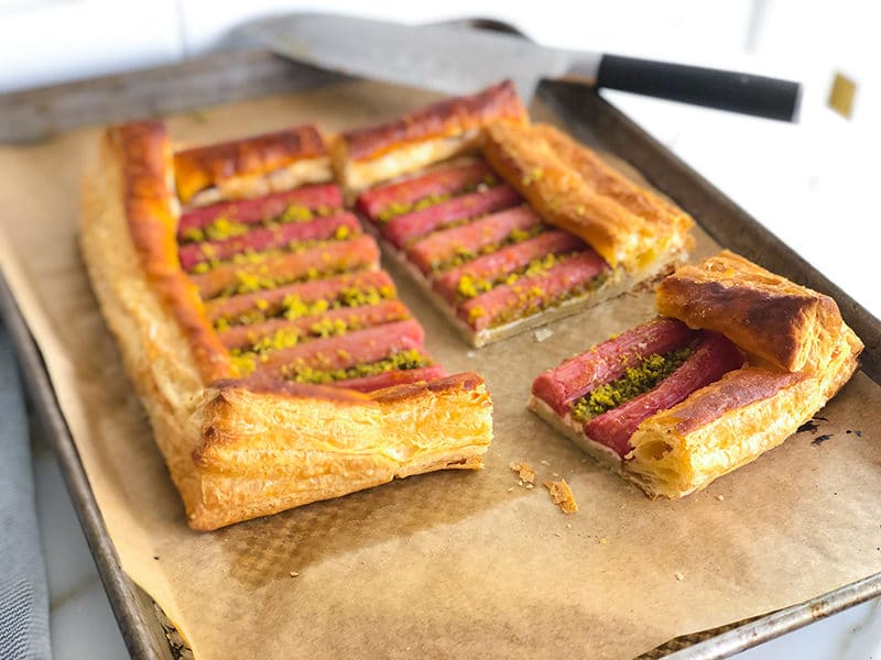 Rhubarb pistachio tart slice on a sheet pan