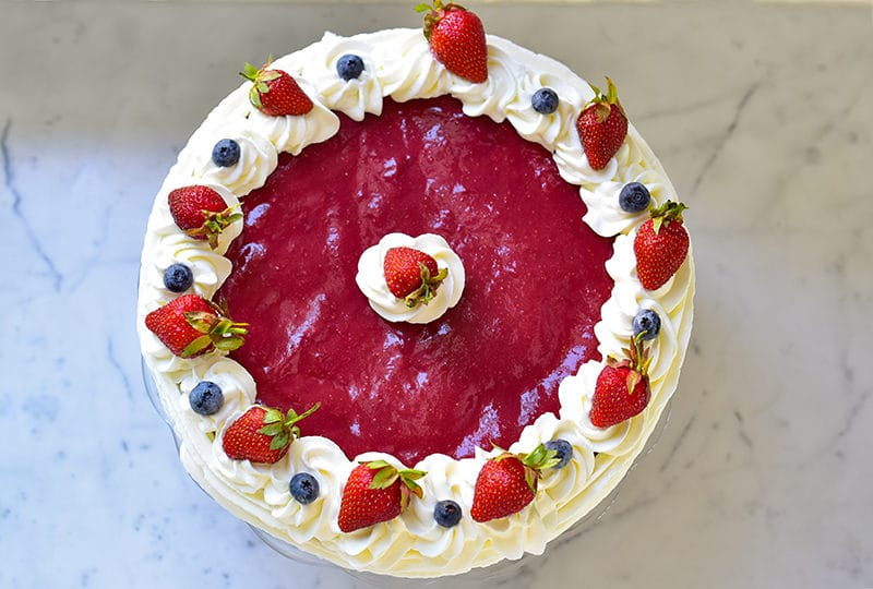 Strawberry cake with blueberries and whipped cream