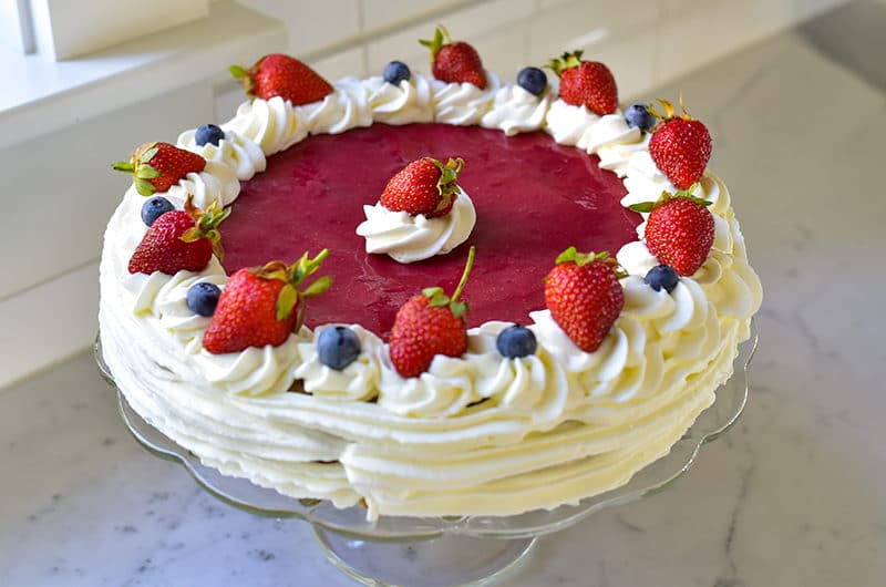 Strawberry Cake with Whipped Cream on a cake stand