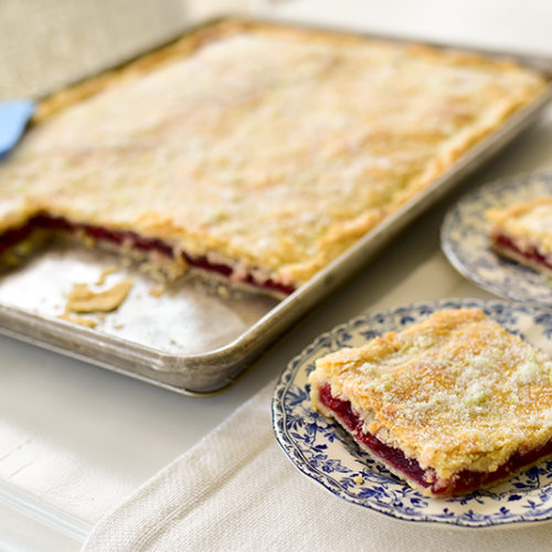 Slices of cherry slab pie pon blue and white plates
