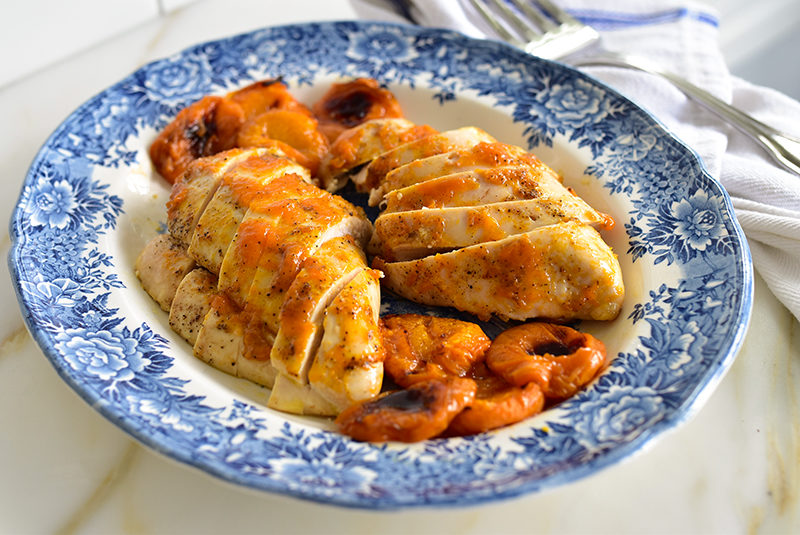 Apricot Chicken sliced with apricots on a blue platter