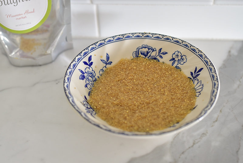 Bulgur wheat soaking in a blue and white bowl