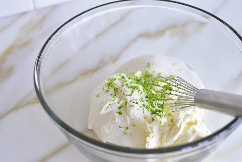 Labneh with cream cheese, sugar, and lime in a bowl with a whisk