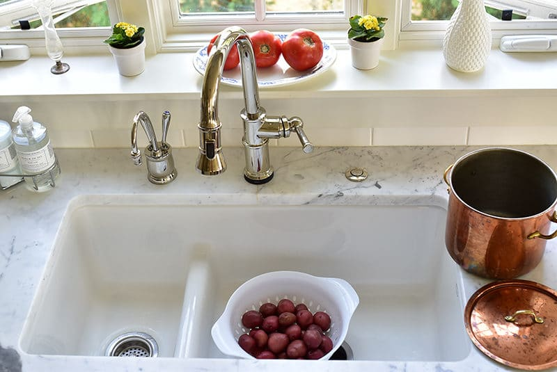 New potatoes in a colander in a white sink with a copper pot