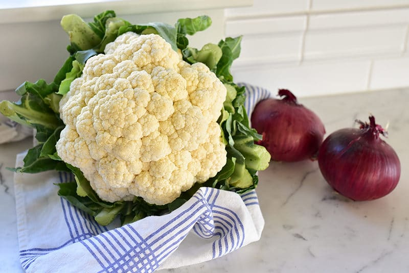 Whole cauliflower on the counter with red onion