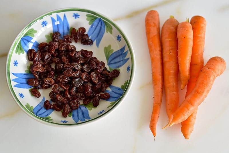 Bunch of carrots next to a blue bowl of raisins on the marble counter