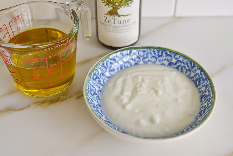 Olive oil in a measuring cup on the counter with a bowl of yogurt