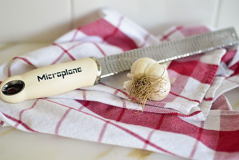Head of garlic on a red plaid towel with a microplane grater