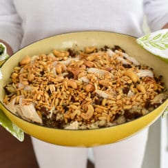 Rice pilaf with nuts in a yellow dish held by two hands