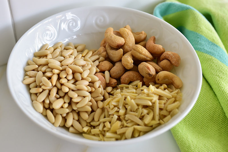 A white bowl with pine nuts, slivered almonds, and cashews
