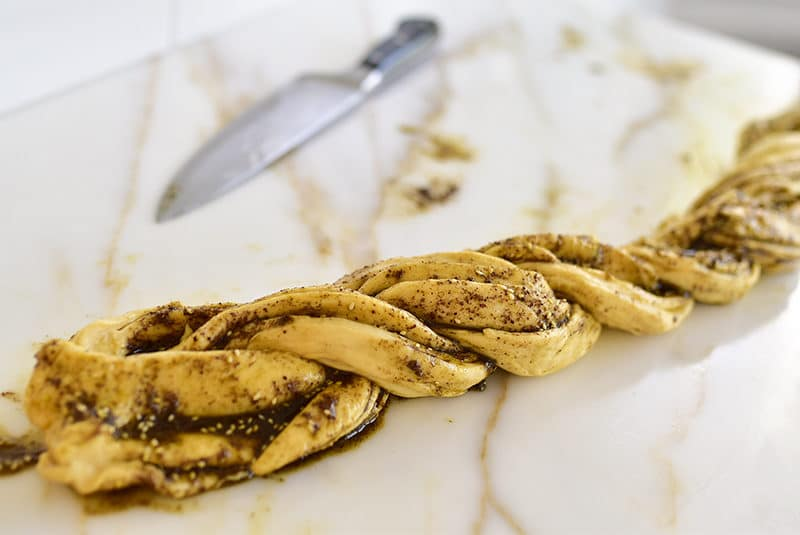 Dough filled with za'atar and olive oil and twisted next to a knife