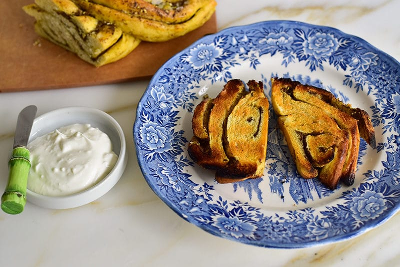 Toasted pieces of za'atar swirl bread with a bowl of labneh