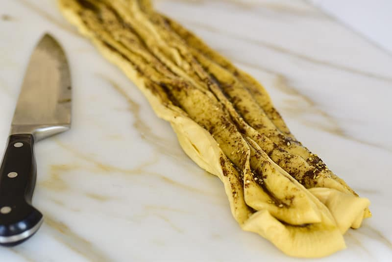 Layers of dough filled with za'atar and olive oil next to a knife