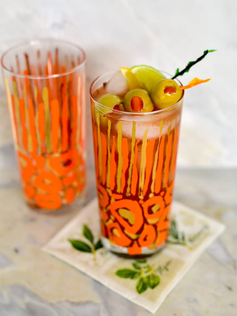 Bloody Mary Cocktail in an orange glass with garnishes on the bar