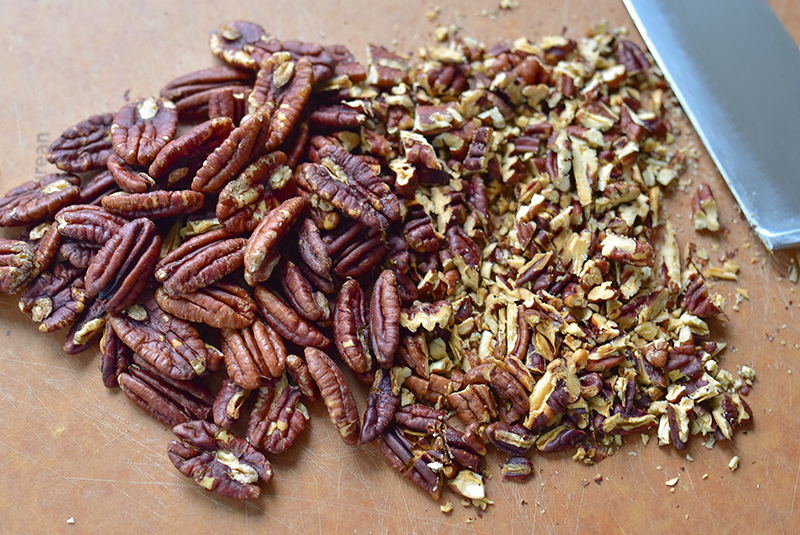 Chopped toasted pecans on a cutting board