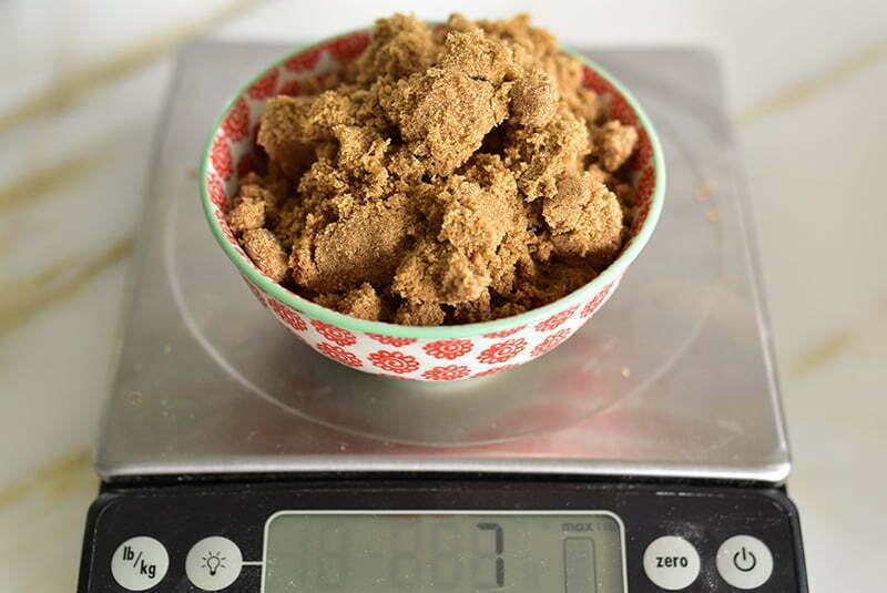 Dark brown sugar on a bowl on a scale.
