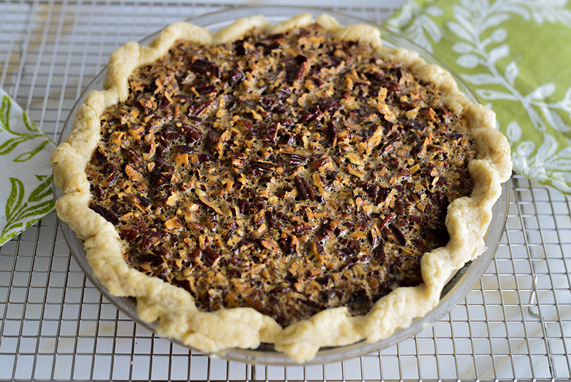 Pecan pie on a rack with green and white pot holders