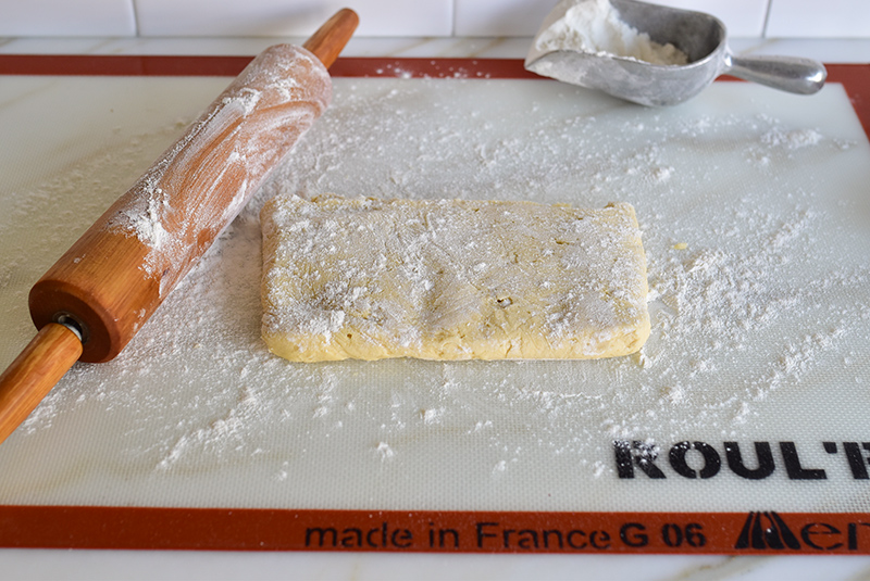 Cookie dough on a silpat with rolling pin and flour
