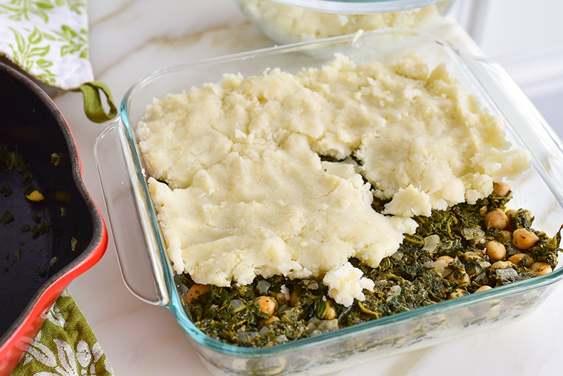 Potato kibbeh top layer in a dish with spinach filling