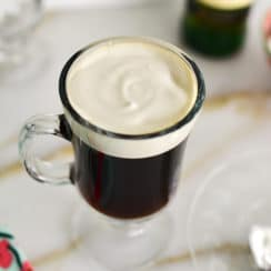 Glass mug of Irish coffee with cream on top