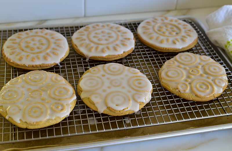 Glazed molded shortbread cookies on a cookie rack