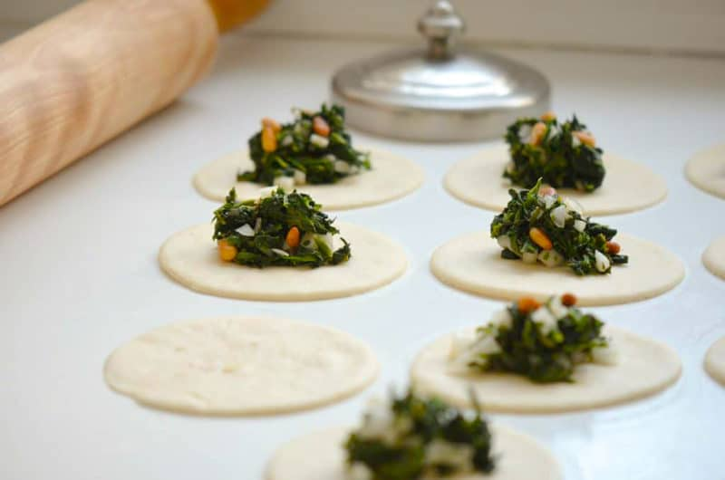 Spinach filling on cut dough rounds with rolling pin and cutter