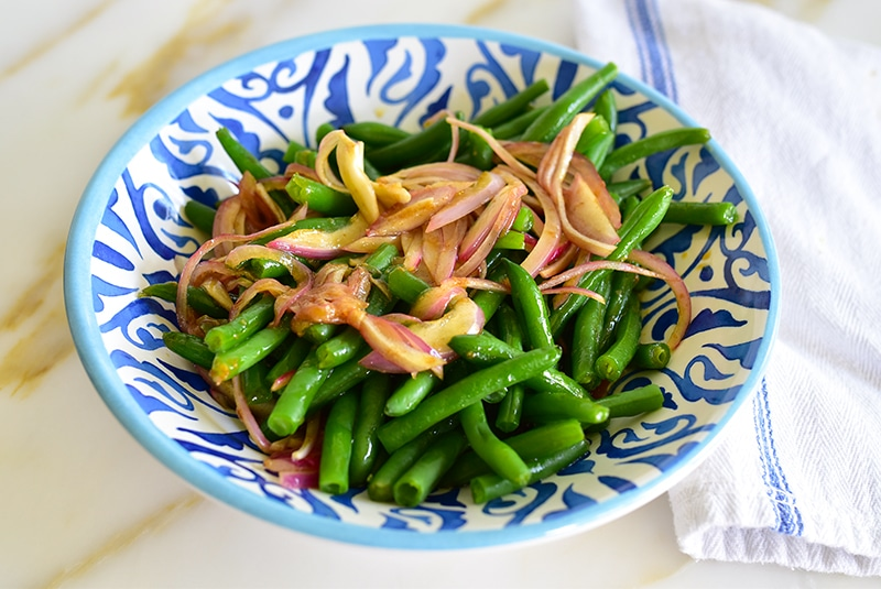 Red onions atop green beans in a blue dish