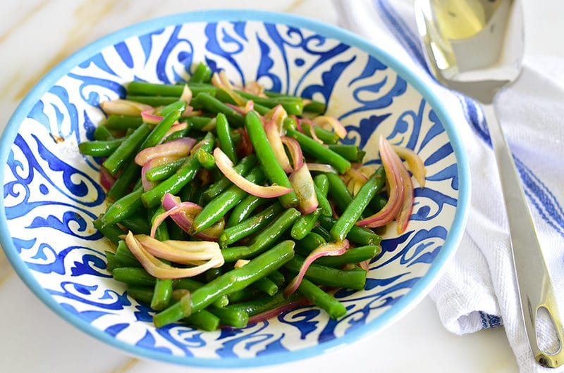Green beans with onions in a blue bowl