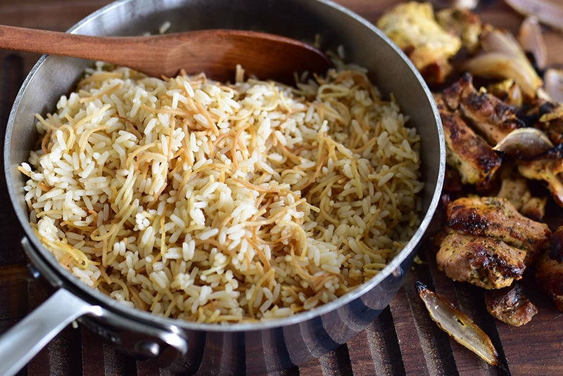 Vermicelli rice in a pot with a wooden spoon and chicken shawarma