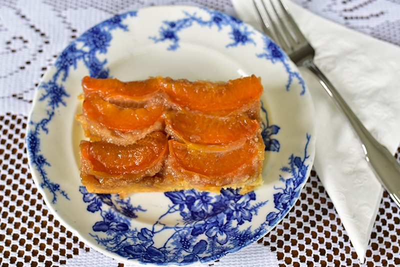 Apricot upside down cake slice on a blue and white plate