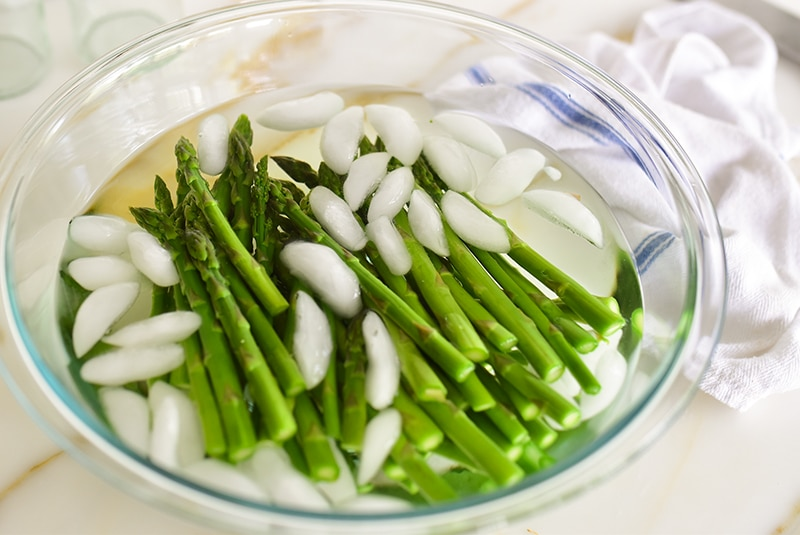 Blanched asparagus in bowl of ice