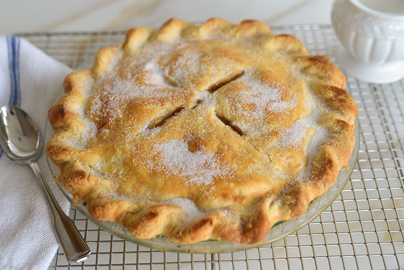 Apple pie on a rack with sugar and spoon