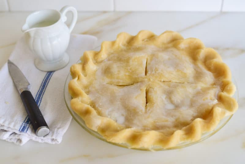 Crimped pie crust topped with milk before baking