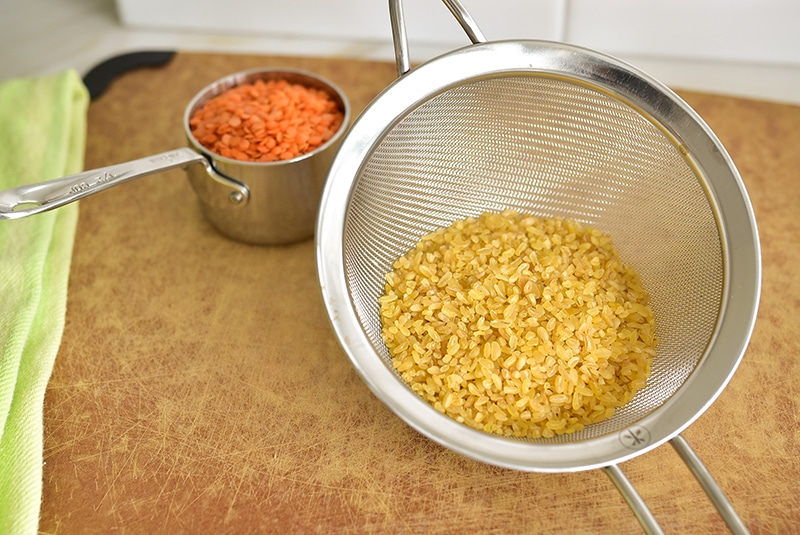 Bulgur and red lentils in a sieve on a cutting board