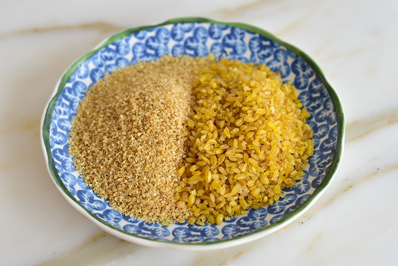 Fine and coarse bulgur side by side in a blue bowl