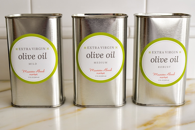 Three tins of olive oil on the counter from Maureen Abood Market